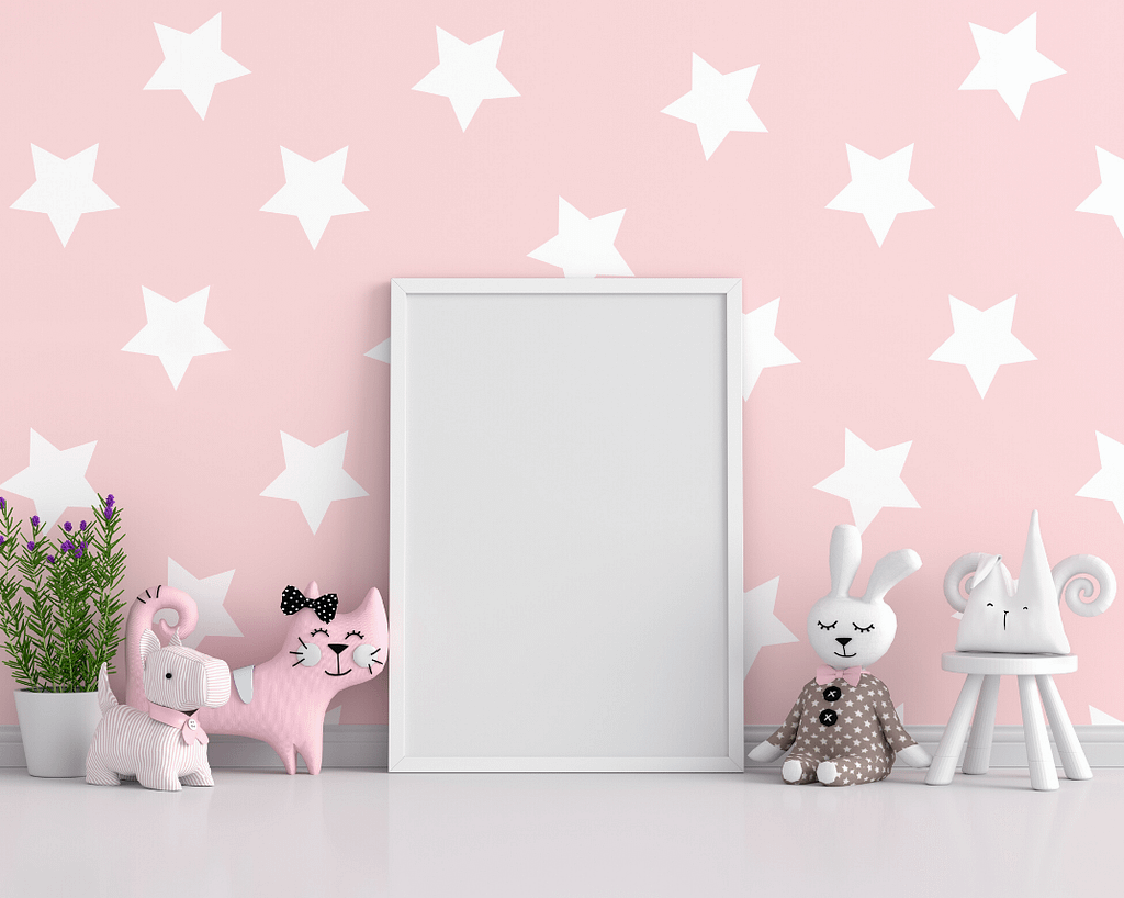Pink wall with stencilled white stars and some toys