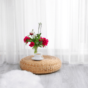 wicker pouffe placed aesthetically in a room with a cup and flower vase
