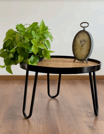 a metal and rattan circular table with a plant and an antique clock