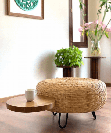 a circular rattan pouffe with a circular attached wooden table