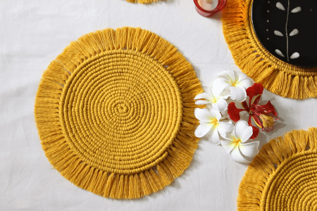 mustard round macrame table mats placed on a table with some flowers