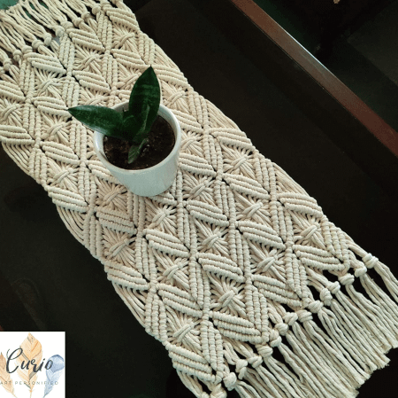 macrame table runner laid on a table and a planter placed on top of the macrame runner