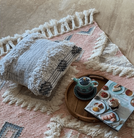a grey hand woven cushion placed over a pink kilim vintage rug for boho effect