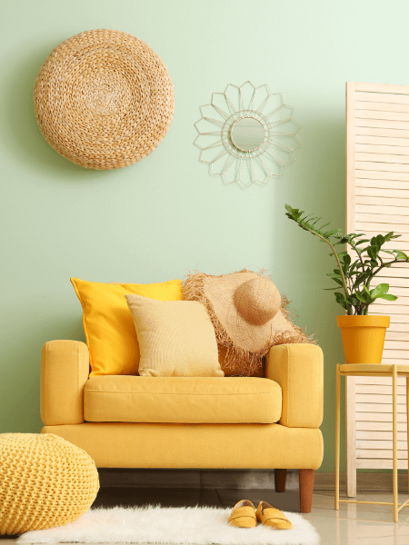 room corner with yellow sofa and rattan wall decor