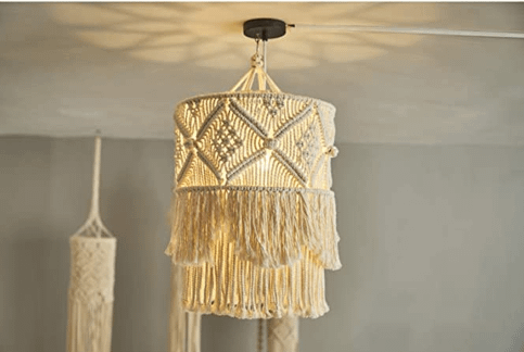 lit macrame chandelier installed on a ceiling of a room