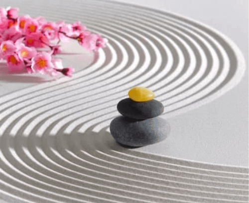 an example of zen garden with white sand, pebbles and flowers