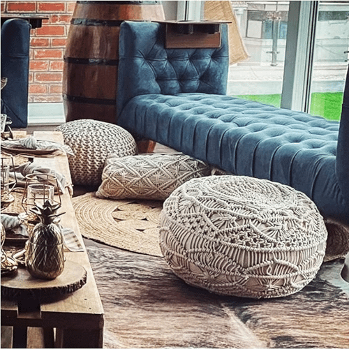 macrame pouffe displayed in a living room with sofa and decorated coffee table