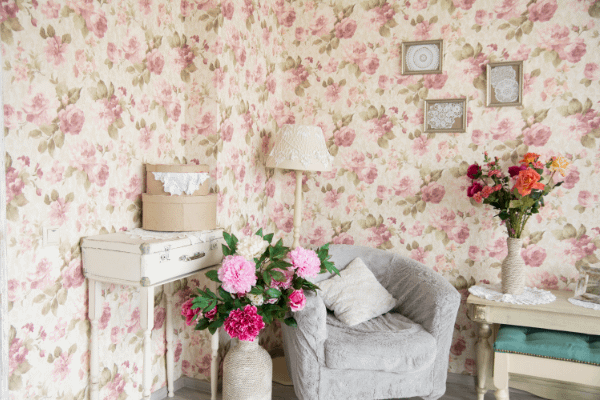 vintage floral wallpaper and furniture arranged in a cottagecore way