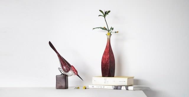 stylised vignette showing a bird, books & vase